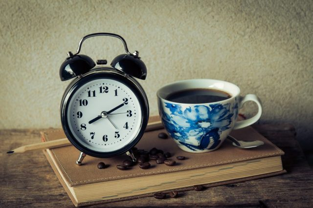 A clock next to a cup of coffee